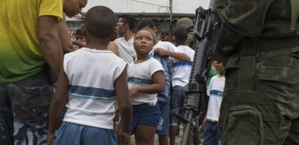 Militares inspecionam mochilas de alunos durante operação na favela Kelson no Rio de Janeiro